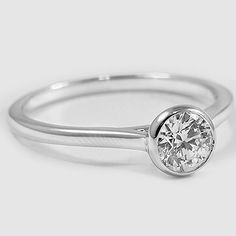 This beautiful modern ring features a bezel set center diamond with a sleek and delicate band for a contemporary look