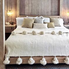 Love the pom pom bed cover and the serene textures and wood together (master?)