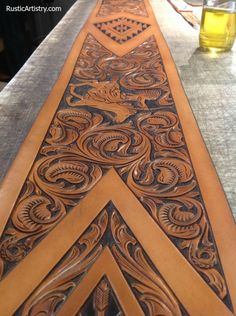 Hand tooled leather panel soon to be applied to the bottom edge of a western leather sofa, with matching tooled arms. https://rusticartistry.com/product/tucson-sofa/
