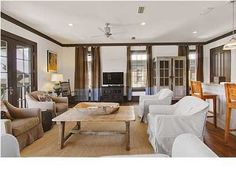 Love the 2 toned curtains, slipcover end shabby chairs, sisal carpet.  The fan should be bamboo.