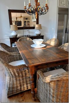 Farm Dining Table matched up with Wicker Arm Chairs with cream cushions...perfect for an upscale coastal beach home.