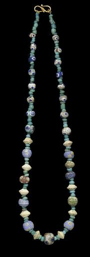 A MEDITERRANEAN GLASS EYE BEAD NECKLACE   PHOENICIAN OR CARTHAGINIAN, CIRCA 6TH-2ND CENTURY B.C.   Composed of twenty-four globular glass eye beads, white, blue, red and pale green in color with compound eyes in blue on white and amber, interspersed with ten biconical white glass beads and small cylindrical and biconical aqua glass beads; strung with a modern S-hook closure  20¾ in. (52.7 cm.) long