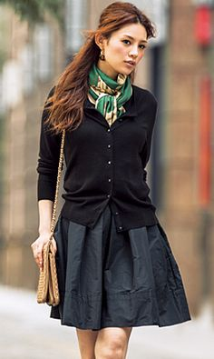 Neck scarf tucked into cardi. A full skirt and cardigan sweater make for a polished outfit.