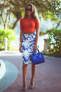 Shop this look on Lookastic:  https://lookastic.com/women/looks/cropped-top-pencil-skirt-heeled-sandals-satchel-bag-sunglasses-watch-bracelet/10230  — Dark Brown Sunglasses  — Red Vertical Striped Cropped Top  — White and Blue Floral Pencil Skirt  — Gold Watch  — Blue Suede Satchel Bag  — Gold Bracelet  — Grey Leather Heeled Sandals