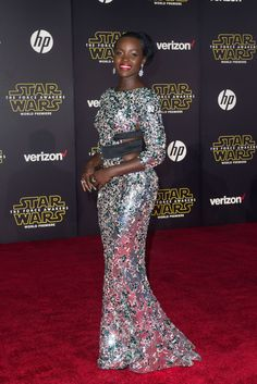 Lupita Nyong'o wearing a silver and green crystal-encrusted gown with black banding at the waist from Alexandre Vauthier Couture