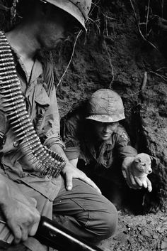 U.S. paratrooper Sgt. James R. Cone, holds a puppy that nipped him as he groped about in a cave entrance on a river bank in Lam Dong Province, Vietnam, July 1966