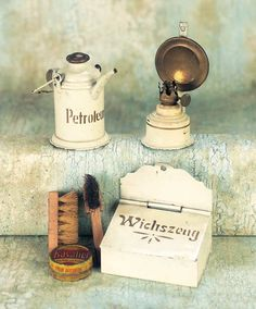 """German kitchen assessories, ca. 1880.  Each is tinplate with painted cream finish and gold stenciling or lettering. Including a Petroleum (gas for oil lamp) can with brass lid and bail handle; box with hanging hole and hinged lid,stenciled """"Wichszeug"""" (old German language for cleaning supplies for shoes or clothes),and a hanging oil lamp with brass back plate. Petroleum can is 2"""" high."""