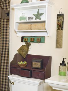 Screw small hooks into vintage wood blocks, and then glue or screw them to a weathered board.  • Shower curtain: http://store.primitivecrossroadscraftbarn.com/shower-curtains/black-applique-star-shower-curtain • Red highback shelf: http://oldefarmcreek.com/store/WsDefault.asp?One=722 • Simplify wax warmer: http://shopheartnhand.com/Simplify-Wax-Warmer.html • Seeds accents: http://kimskountrykreations.com/store/WsDefault.asp?One=1562