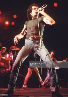 Bon Scott performs on stage with AC/DC by Michael Putland.