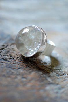 Un cristal clair et lumineux brésilien Crackle Quartz est magistralement poli dans une bulle taille joyau pour cette bague adorable et unique.