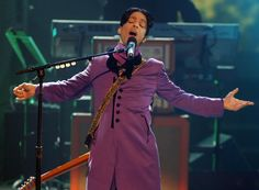 All-purple-everything was the call for Prince, who hit the stage in a long purple jacket with prominent buttons, matching pants, a scarf, and a guitar with a supercool animal print strap slung over his shoulders. (Photo: Getty)