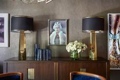 ChrisLevine's holographic portrait of Queen Elizabeth II is installed in the dining room, and flanked by solid brass table lamps from HUDSON NEW YORK. They sit on a French oak and antique bronze cabinet from JEANDEMERRY.