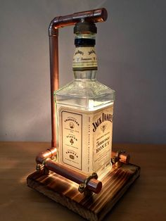 At Home Stuff Handmade Jack Daniels Lamp. This retro lamp is bang on trend! Will be a talking point at any party! Lamp comes with an inline switch, plug and 2 metre cable The copper surrounding the bo Lampe Jack Daniels, Jack Daniels Bottle, Lighted Wine Bottles, Liquor Bottles, Empty Bottles, Liquor Bottle Lights, Glass Bottles, How To Make Diy Projects, How To Make Lamps