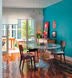 Na casa da designer Ana Maria Mouawad Queiroga, a mesa de jantar recebeu irreverentes cadeiras diferentes. A parede turquesa recebe a iluminação que vem pela porta de vidro (que substitui a janela) e uma cortina rolô controla a luminosidade do ambiente.
