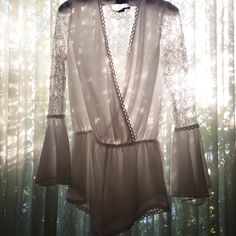 Trumpet sleeve chiffon romper featuring lace sleeves and back. Partially lined. ABOUT - 100% Polyester - Hand wash cold - Imported SIZE + FIT - Model is wearing a small RETURNS & SHIPPING All US order