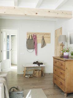 perchero y comoda de madera de una habitación con vigas vistas