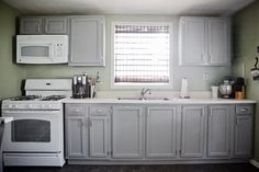 Gray cabinets, green walls, white appliances.  Cabinets are painted a tweaked version of Thunder by Benjamin Moore.  Walls are Urban Nature by Benjamin Moore.  Blinds and hardware Allen + Roth.  Next up, new countertops, backsplash, sink, and hopefully a rustic wooden island with metal stools?