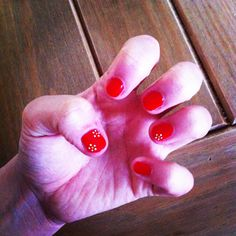 Red manicure with miniature white flowers on ring finger nail and thumb nail.