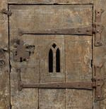 """A small oak boarded cupboard In the manner of a 15th century aumbry Having a boarded top, the central boarded cupboard door with central Gothic lancet aperture, flanked to either side by broad uprights, the sides descending to V-shaped cut-away supports, 64cm wide x 27.5cm deep x 80cm high, (25"""" wide x 10.5"""" deep x 31"""" high)"""