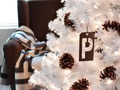 Instead of typical ball-shaped ornaments, give your tree streamlined, graphic impact by stringing metal stencils from the hardware store onto twine. Create a similar look with cardboard stencils by punching a hole through the top, then hanging with twine.
