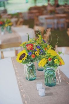 Bouquets in mason jars. Only yours would not be blue and flowers would have more purple. Burlap is a nice runner too. Throw in some tea lights ...