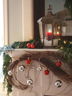 Use Candles - 30 Stunning Ways to Decorate Your Living Room This Christmas.  I love everything about this Christmas mantle from the lantern to the curled vines with red & silver ornaments hanging from them!  I have to remember to cut back & keep my vines from the summer next year!!!
