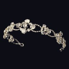 """Perfect for the modern bride, this tiara features a pattern of silver loops and stunning rhinestones. The ornamentation continues to both ends of the tiara, measuring 13"""" wide and 1"""" tall at its cente"""
