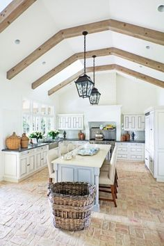 Kitchen with white cabinets, grey counters, vaulted ceiling and pale brick floor