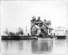 A rear view of the Grassy Island Lighthouse. Ryan Northrop, keeper (crossed arms), John Bryan (in boat) and Mrs. Bryan. Gift of Daisy Henning, July 1, 1957.