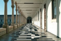 a carpet cut into a graphic interpretation of the numbers and letters which form data protection patterns lines the first level loggia of the universita degli studi di milano. Historical Architecture, Architecture Design, Walking Paths, Asymmetrical Design, Patterned Carpet, Kitchen Interior, Stairs, Typography, Flooring