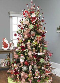 guirlandes en rouge et blanc et petites statuettes de père Noël accrochées au sapin de Noël