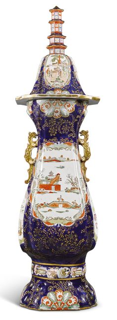 A massive Mason's Ironstone hall vase and cover, circa 1830-45  of baluster square section with chamfered fluted corners, printed and coloured with shaped panels enclosing chinoiserie figures at various pursuits, reserved on a deep-blue ground heightened with ochre flowering trails, set with iron-red and gilt chilong handles, the domed cover similarly decorated and surmounted with a pagoda,  152cm