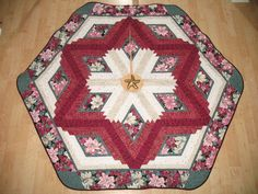 Quilted Christmas Tree Skirt constructed of 100% cotton fabrics of deep burgundy and whites with poinsettias in burgundy and pink and gold accents...  Your tree will never look neglected before or after the presents are displayed under it with this beautiful heirloom tree skirt wrapped around the base of it...  Makes a fabulous gift for a Hostess, birthday, anniversary and how wonderful for newlyweds first Holiday together when given as a Wedding present. . .