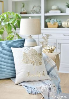 Coastal Fall Decor Home Tour in a soft color palette of blues, grays, whites & metallics. These pretty fall pillows and plaid throw from HomeGoods add cozy warmth to the familyroom. sponsored