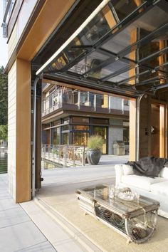 Interior room transforms to an outdoor living space with windows that roll up like a garage door. They look gorgeous when closed. Gig Harbor, WA. Scott Allen Architecture.