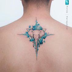 Tatuagem criada por KORAY KARAGÖZLER da Turquia. Elefante com fundo colorido em tons de azul nas costas.