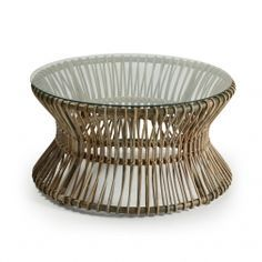 Een rattan salontafel met een ronde glazen bovenplaat