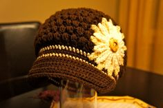 "A ""Sporty Puff"" Crocheted Child's Hat with an oversized flower and a visor. $20.00, via Etsy."