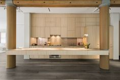 A kitchen island is suspended between two columns.