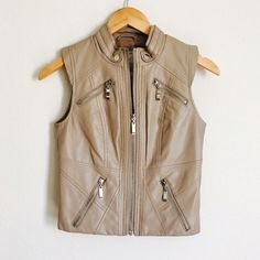 Tan Faux Leather Zip Vest Gorgeous tan faux leather zip vest from Buckle. Pieces fabric with cap sleeves, silver zippers and polyester lining. Worn only a few times. Faint pen mark on front near zipper (see last photo). Size small, will also fit XS. BKE Jackets & Coats Vests