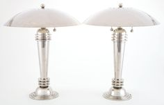 A PAIR OF AMERICAN ART DECO CHROMED METAL DESK LAMPS Maker unknown, American, circa 1935. The ringed torpedo-form lamps rising from hemisphere on stepped base, dome shade with perforated ring around spherical finial.