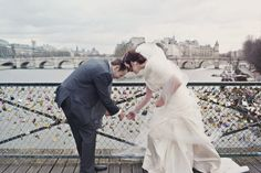 Newlyweds add their own padlock to a bridge in Paris. The locks symbolize everlasting love.