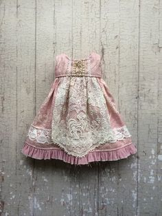 This dress is made from a three different toning dusty pink cottons. It has a delicate apron made from vintage lace, and a frayed ruffle hem. A simple but very sweet dress, fastens at the back with a snap. Please note that the lace used in these dresses is very old, so may well have