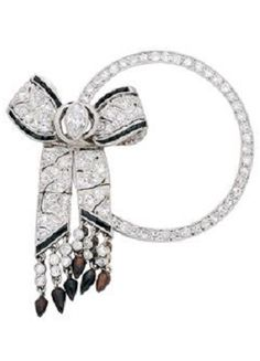 A Diamond and Onyx Brooch, circa 1920. The circular row of round diamonds applied with a ribbon bow and sashes set with marquise-cut and round diamonds and onyx trims, and suspending diamond tassels with onyx finials, mounted in platinum.