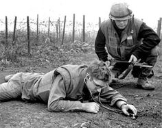 """Khe Sanh, South Vietnam, March 1968: US Navy Hospital Corpsman Theodore Rutkowski of Pittsburgh lies on the ground just outside of Khe Sanh's outer defenses and uses a stethoscope to listen for signs of Viet Cong tunneling beneath the beleaguered base. Covering him is US Marine Julian Kalama of San Lorenzo, Calif."" Photographed by John Olson for Stars and Stripes"