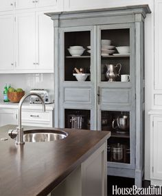 Designer Samantha Lyman wanted to give a new California kitchen some historic pieces like this antique armoire. It was originally only 12 inches deep inside – not big enough for large platters and big bowls. So Lyman set it into the cabinetry to give it more depth. The cabinet-maker removed the back and extended it to 26 inches inside. Then, Lyman painted the interior a darker color to conceal the difference.   - HouseBeautiful.com