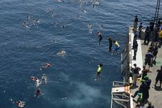 Sailors from the aircraft carrier USS Dwight D. Eisenhower jump into the North Arabian Sea.