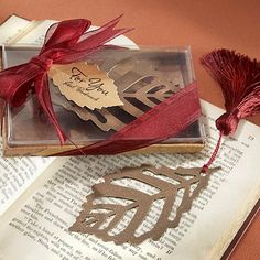 Give guests charming wedding favors that will be a daily reminder of your fall wedding with turning leaves bronze metal leaf bookmarkers with burgundy tassel.