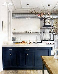 "Navy blue kitchen base cabinets in a minimalist kitchen with an industrial vibe. Lots of chrome makes it crisp. Pink flowers because pink and navy always play well together.   (Jenna Lyons of j.crew)  To see more of the blue cabinet trend, follow Jill Jordan's board ""Blue Cabinets""."