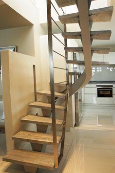 Vu d'ensemble de cette escalier deux quarts tournant limon central en acier peint et marches en chêne.